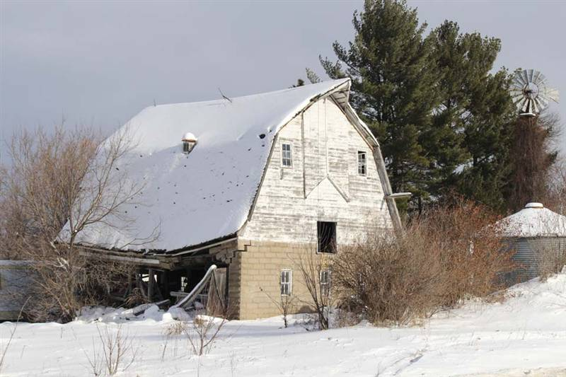 Snow covered barn with collapsing roof